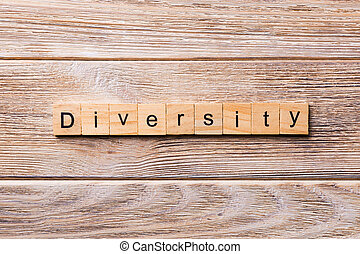 Diversity word written on wood block. Diversity text on wooden table for your desing, concept