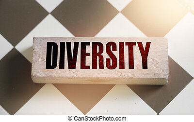 Diversity word written on wooden block on chess board. Selective focus. Equality and diversity concept