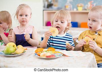 divertido, niños, grupo, comida, fruits, en, jardín de la infancia, dinning, habitación