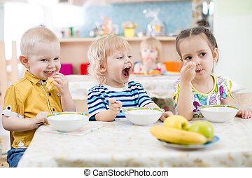 divertido, poco, niño, con, tapa, comida, en, jardín de la infancia, grupo