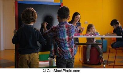 Divese boys drawing at blackboard in kindergarten