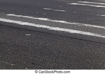 Erased road markings at the crossing point through the pedestrians. Photo close-up of a black asphalt road