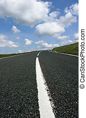 Uphill road featuring the central white line and a blue sky with cumulus clouds.