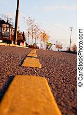 Yellow dividing line on asphalt road