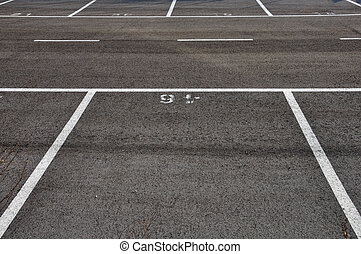 Dividing lines in empty asphalt paved parking lot abstract background.