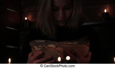 Charlatan witch reading book of black magic, view on burning candle. magic ritual. old book and candle