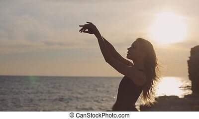 Divine girl clothed in long black dress standing near the sea at sunset with a sense of harmony