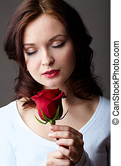 Divine smell - Portrait of attractive woman holding red rose...