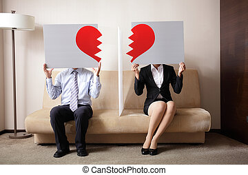 Divorce - Sad young couple holding billboard sign with break...