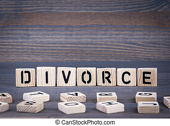 Divorce word written on wood block. Dark wood background with texture
