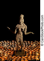 Diwali. Traditional bronze statue of Hindu Goddess Lakshmi or Laxmi in flaming candle light.