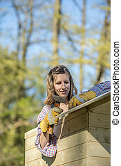 DIY concept - young woman holding a hammer working on a wooden playhouse