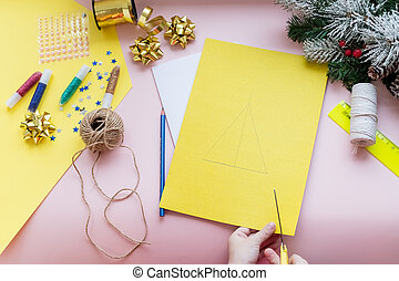 DIY concept.How to make Christmas card.New Year idea for children. Step-by-step photo instructions. card with christmas tree.Children's creativity.Step 2.Kid holds scissors and cuts a tree from paper.