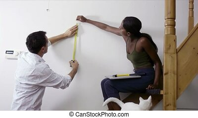 Diy, couple measuring wall at home - Do it yourself, couple...