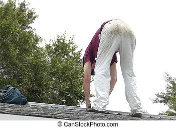 DIY Homeowner Repairing Roof Leak - A homeowner is on the...