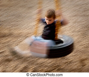 Dizzy - Young boy on tire swing twirling