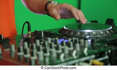 Dj adjusts the tempo on the mixing panel.