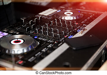 In selective focus of Pro dj controller. The DJ console cd mp4 deejay mixing desk Ibiza house music party in nightclub with colored disco lights.
