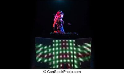 DJ blonde woman in a neon light behind the decks