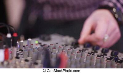 Male DJ Controls sound remote and laptop
