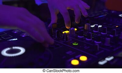 DJ console for mixing dance music and colorful light in...