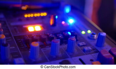 DJ console mixing tracks - A DJ behind the console, on...