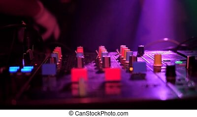 DJ console, party dancing people on the dance floor. Light music changing light.