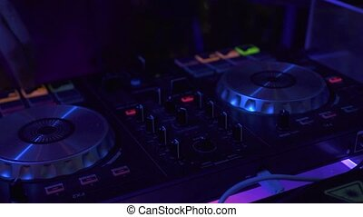 DJ control music console and colorful light in nightclub. DJ...