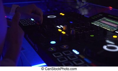 DJ controller and music console in colorful light at dance...