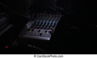 DJ controls sound console at the concert, close-up