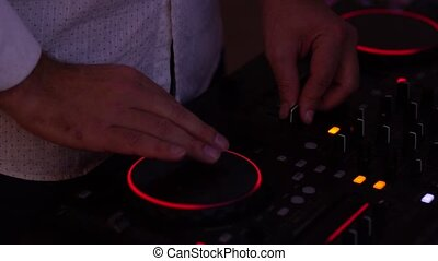 DJ controls the music console in a nightclub. - DJ hands on...