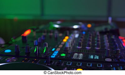 Dj desk console mixer and man's hands. Knobs and buttons....