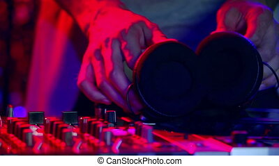 Low section of unrecognizable disc jockey putting on headphones and mixing at dj panel