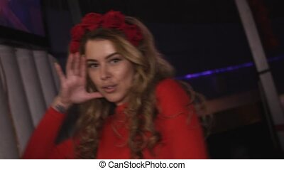 Dj girl in red dress dancing at turntable in nightclub. Hands movements.