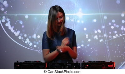 Brunette DJ girl in black on decks at the club dancing