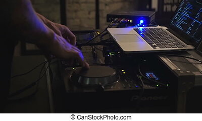 Dj hands on equipment deck and mixer with record at cafe