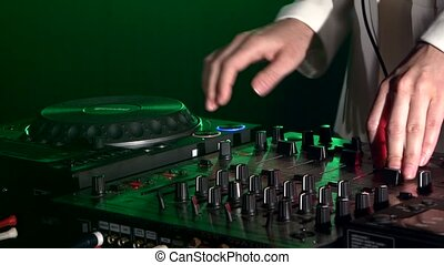 Dj hands on equipment deck, dancing and playing, close up, green backlight