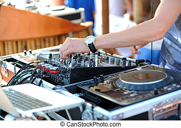 A detail of dj who is mixing the track on the beach party