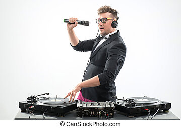 DJ in tuxedo having fun and dancing with microphone by the turnt
