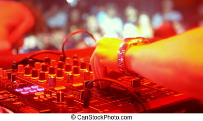 Dj mixer controller in night club disco party. DJ Hands touching buttons and sliders playing electronic music