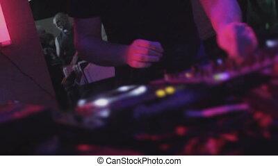 """DJ mixing music at nightclub, live broadcast on radio station"""