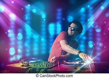 Dj mixing music in a club with blue and purple lights -...