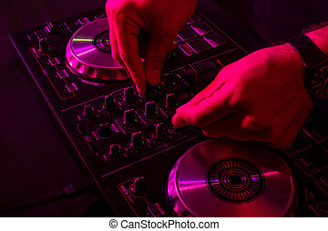 Dj mixing on turntables with color light effects. Soft focus on hand. Close-up.