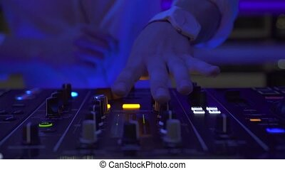 Dj playing dance music on sound console at event party in...
