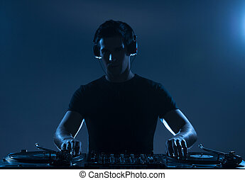 DJ playing music. Confident young DJ spinning on turntable...