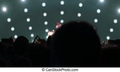 Dj playing the track in front of a dancing crowd on stage