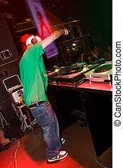 DJ playing turntable in the club - Hip-hop deejay rocking...