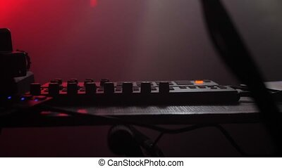 DJ plays a set at the party. Musical equipment. Light from party lights. Event