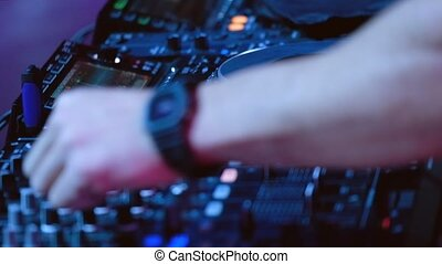 DJ plays mix on controller at a disco in the nightclub