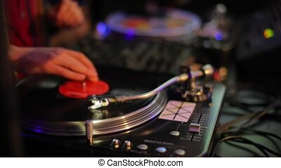 DJ plays vinyl record electronic music at a club party. Makes scratch records, adjusts the equalizer.